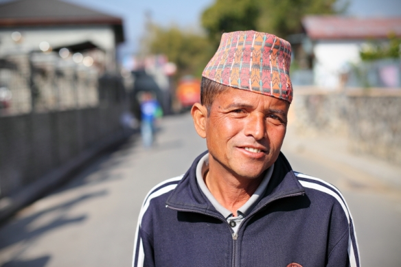 man walking in back streets of pokhara, nepal