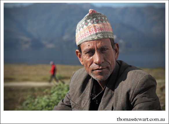 man with traditional nepalese hat kneeling at lakeside in pokhara, nepal